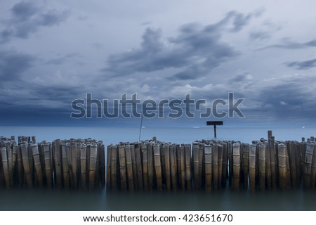 Bamboo breakwater on the sea coast with hard storm background - stock photo
