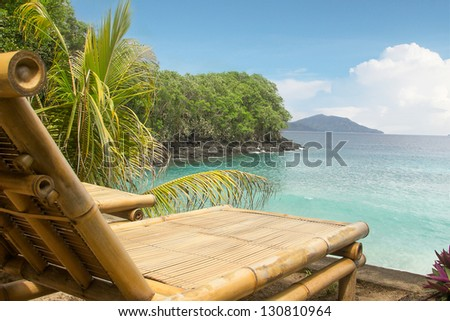 Bamboo chair on a small private beach overlooking a blue ocean for a summer holiday in a tropical paradise