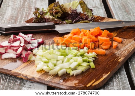 bamboo cutting board with chef's knife with freshly chopped organic carrots, lettuce, celery, and radishes - stock photo