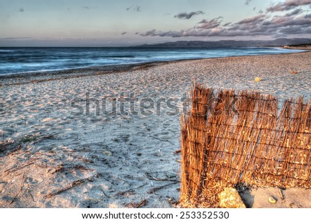 bamboo fence by the sea in Sardinia. Processed for hdr tone mapping effect - stock photo