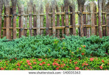 Bamboo fence with plants and flower.