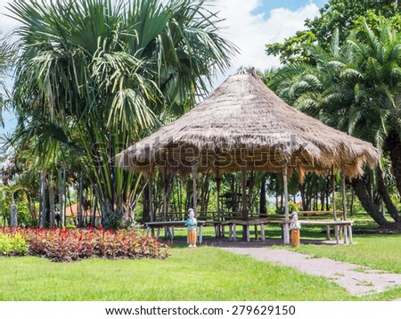 bamboo gazebo with straw roof in the park - stock photo
