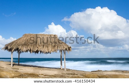 Bamboo hut on a tropical beach with white puffy clouds in sky - stock photo