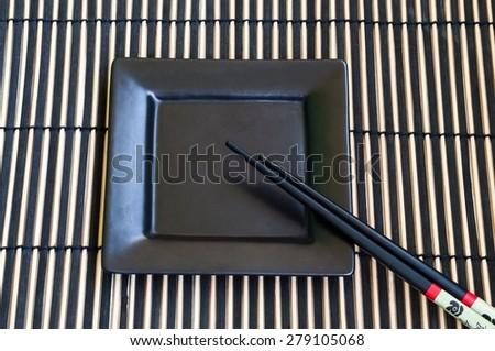 Bamboo mat, chopsticks and a black ceramic plate - stock photo