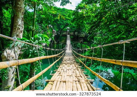 Bamboo pedestrian suspension bridge over river in tropical forest, Philippines - stock photo