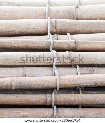 Bamboo raft with the old rope is floating in the lake - stock photo