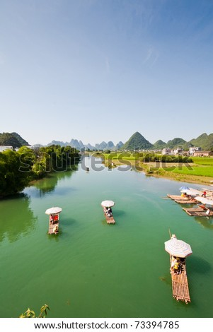bamboo river boats drifting on the river in yangshuo guillin , china. - stock photo
