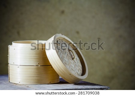 Bamboo round container shape for steaming asian food, Japanese Chinese Vietnamese on brown background - stock photo