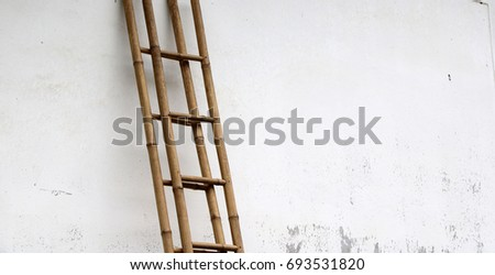 Bamboo Stairs Leaning Against The Wall. The Stairs On The White Mortar Wall  Of House
