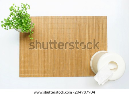 Bamboo table mat with a small plant and a tissue box - stock photo