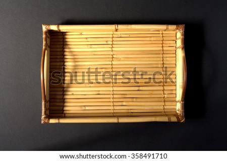 Bamboo tray on black background - stock photo