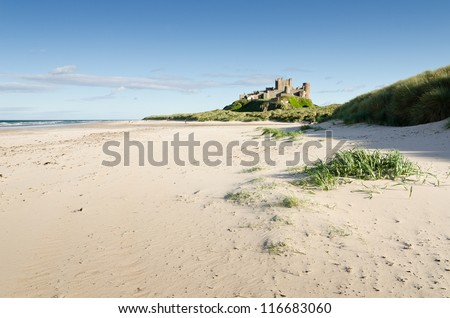 Bamburgh Castle from beach / Bamburgh Castle taken here from the north beach dates back to the 6/7th century - stock photo