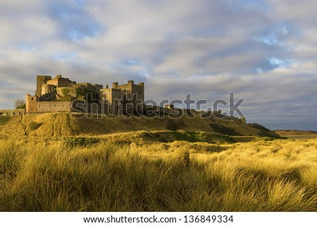 Bamburgh Castle in Northumberland viewed from the sand dunes - stock photo