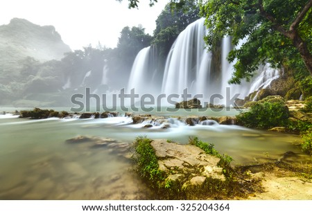 Ban Gioc Waterfall flickers inside the canopy with the path pedestal foot waterfall to create rapids for waters flowing through the soft mist splashed beautiful - stock photo