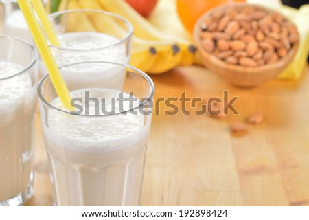 Banana and almond milk smoothie in a glass on a kitchen table. Summer drink made of banana, almond milk and few dactyl. Copy space. - stock photo