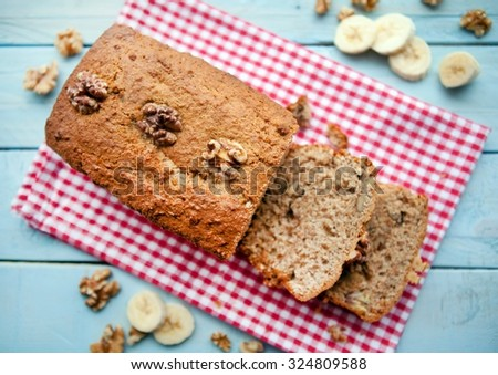 Banana and Walnut loaf cake cut open on red and white gingham cloth - stock photo