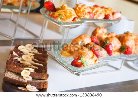 Banana bread with banana slices and various pastries in the background - stock photo