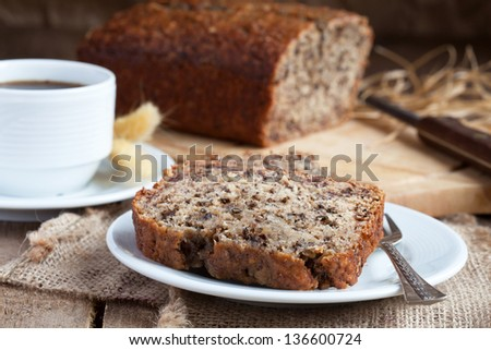 Banana bread with nuts with cup of coffee in rustic style - stock photo