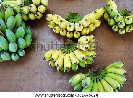 Banana bunch both raw and ripe on wooden table  - stock photo