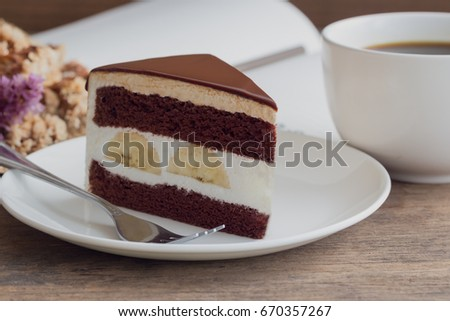 Banana chocolate cake on white plate served with black coffee.