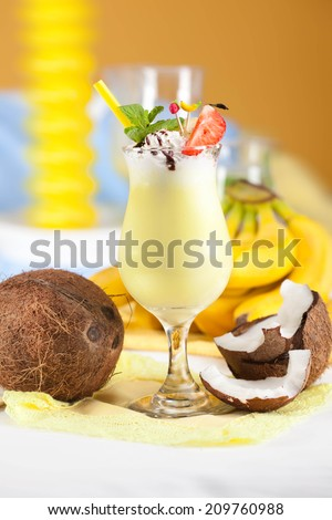banana cocktail with coconut milk in a glass with a straw in a still life - stock photo