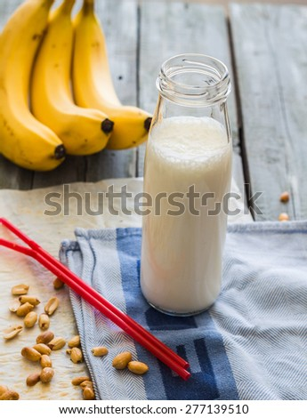 banana cocktail with peanut butter, roasted peanuts, drink on a light background - stock photo