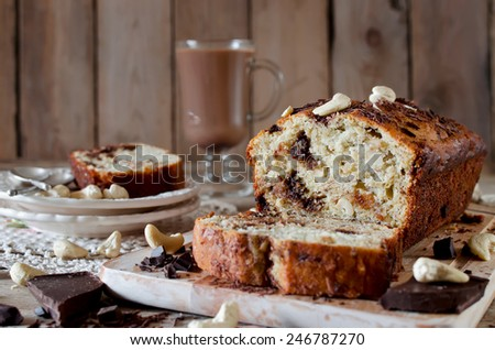Banana cupcake with chocolate and cashew nut. On the wooden table cupcake and chocolate drink - stock photo