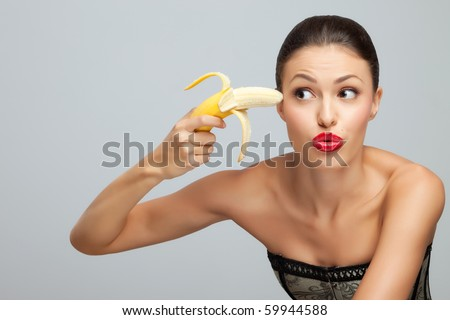 Banana gangster. A portrait of a beautiful sexy lady trying to kill herself with banana. - stock photo