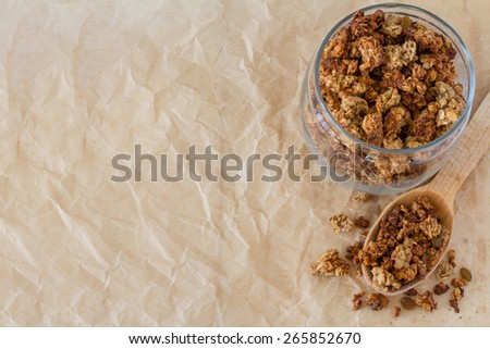 Banana granola in glass jar and wood spoon, paper background, top view - stock photo