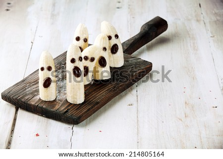 Banana Halloween Ghosts with Chocolate Faces on Wooden Cutting Board - stock photo
