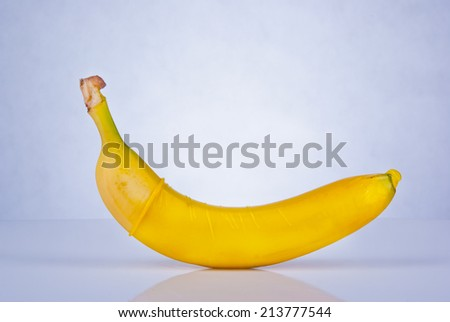 Banana in yellow condom  - stock photo