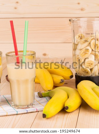 Banana juice and blender full of sliced fruits. Wooden background.