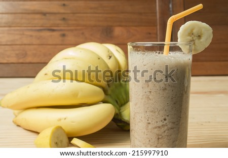 Banana juice on a wooden table - stock photo