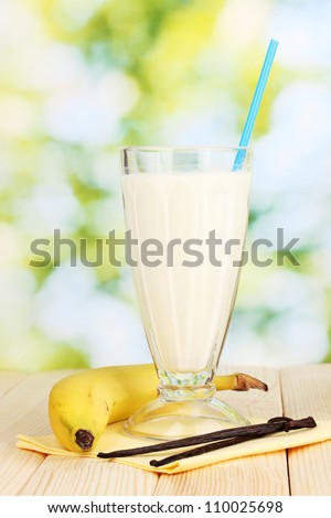 Banana milk shake on wooden table on bright background