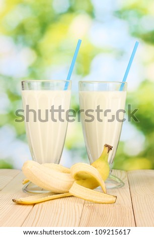 Banana milk shakes on wooden table on bright background