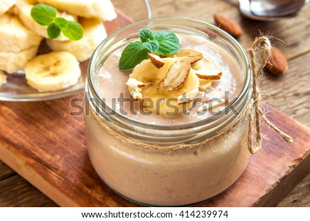 Banana mousse with almond and mint for healthy vegetarian dessert over rustic wooden background - stock photo