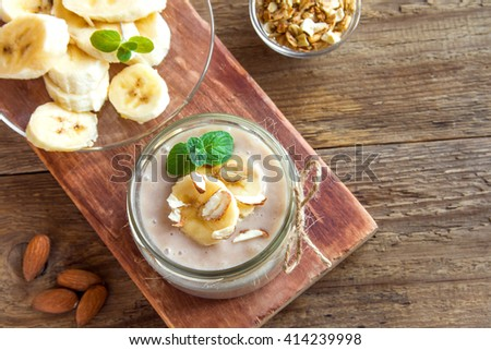 Banana mousse with almond and mint for healthy vegetarian dessert over rustic wooden background with copy space - stock photo