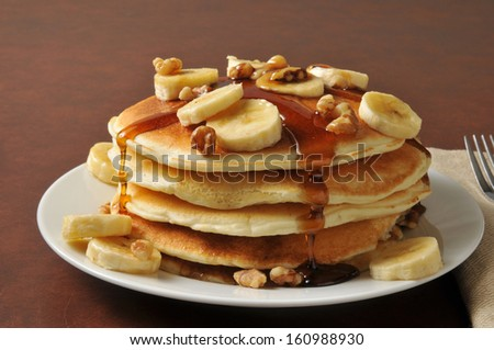 Banana nut pancakes with syrup - stock photo