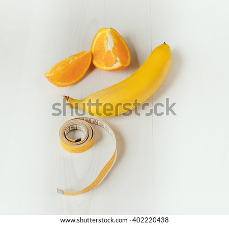 Banana, orange slices and measuring tape - stock photo