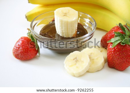 banana's and strawberries with chocolate dipping sauce. - stock photo