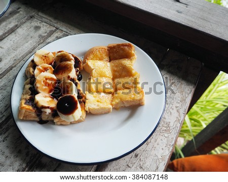 Banana slice with Sweetened condensed milk and chocolate topping on toast on wood table. - stock photo