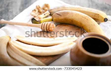 Banana slices on a plate with honey being poured onto them