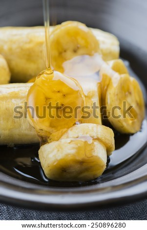 Banana slices with honey syrup in a black vintage dishware.  - stock photo