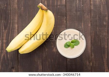 Banana smoothie and fresh banana on wooden table. - stock photo