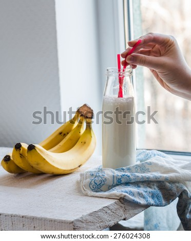 banana smoothie in a glass bottle, fresh bananas, drink on a white background - stock photo