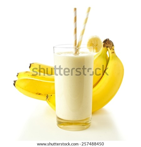 Banana smoothie in a glass with straws over white, bananas in background - stock photo