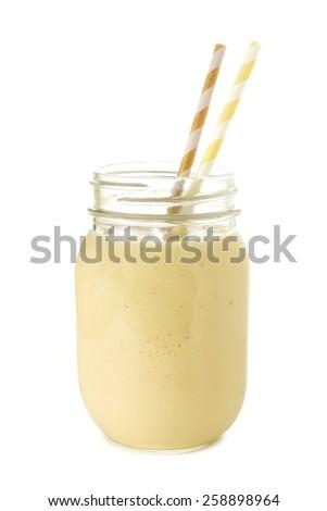 Banana smoothie in a mason jar with straws over white - stock photo