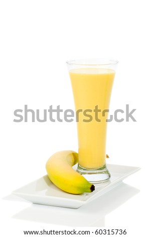Banana smoothie in tall glass on white background - stock photo