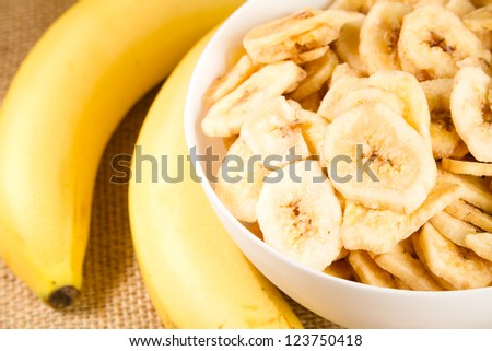 Banana - This is a close up shot of a bowl full of dried banana chips. Shot with a shallow depth of field and vignetting. - stock photo