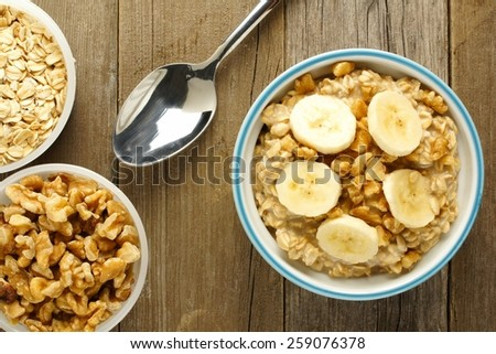 Banana walnut overnight oatmeal in a bowl on wood table, overhead view - stock photo